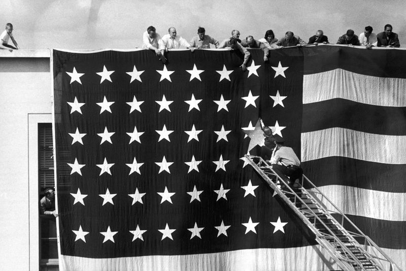 A photo from 1958 showing a very large American flag held against a building and men on a ladder pinning an additional star to its star field. Several people hang over the roof edge of the building to watch.