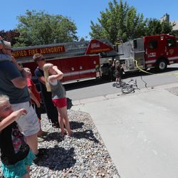 Residents watch Unified Fire Authority firefighters fight a fire at 3381 S. 3170 East in Millcreek on Sunday, July 5, 2020.