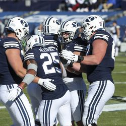 Brigham Young Cougars running back Tyler Allgeier (25) is congratulated by the BYU offensive line after scoring a touchdown during a game against North Alabama in Provo on Saturday, Nov. 21, 2020.