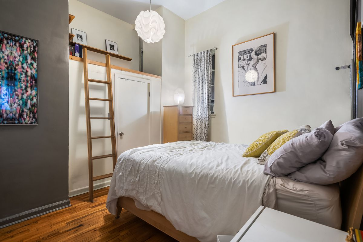 A bedroom with a small bed, hardwood floors, and beige walls.