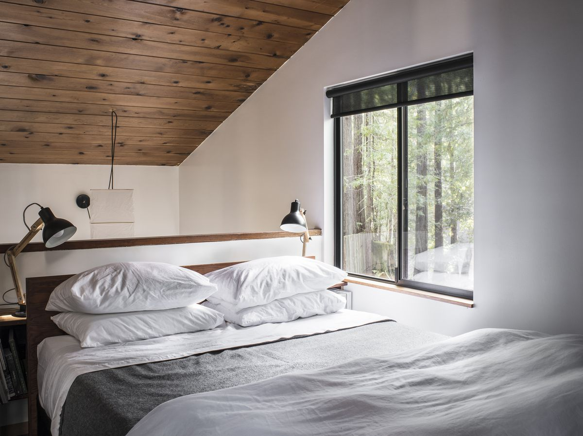 A bed with white sheets and a gray blanket sits in the loft. The ceiling is composed of wood. Wood and metal reading lamps flank the bed.
