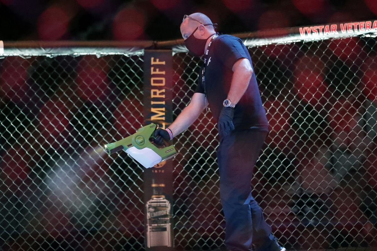 A worker sprays sanitizer in the octagon between bouts during UFC 249 on May 9, 2020, in Jacksonville, Fla.