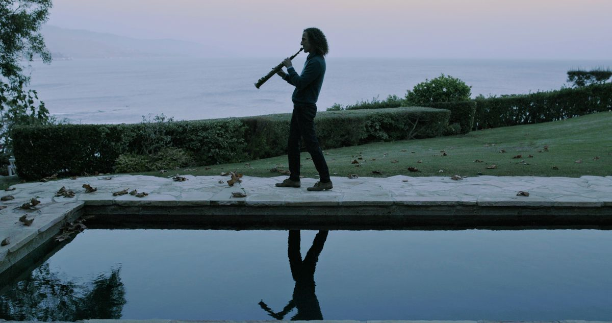 Kenny G, in silhouette, plays near a pool.