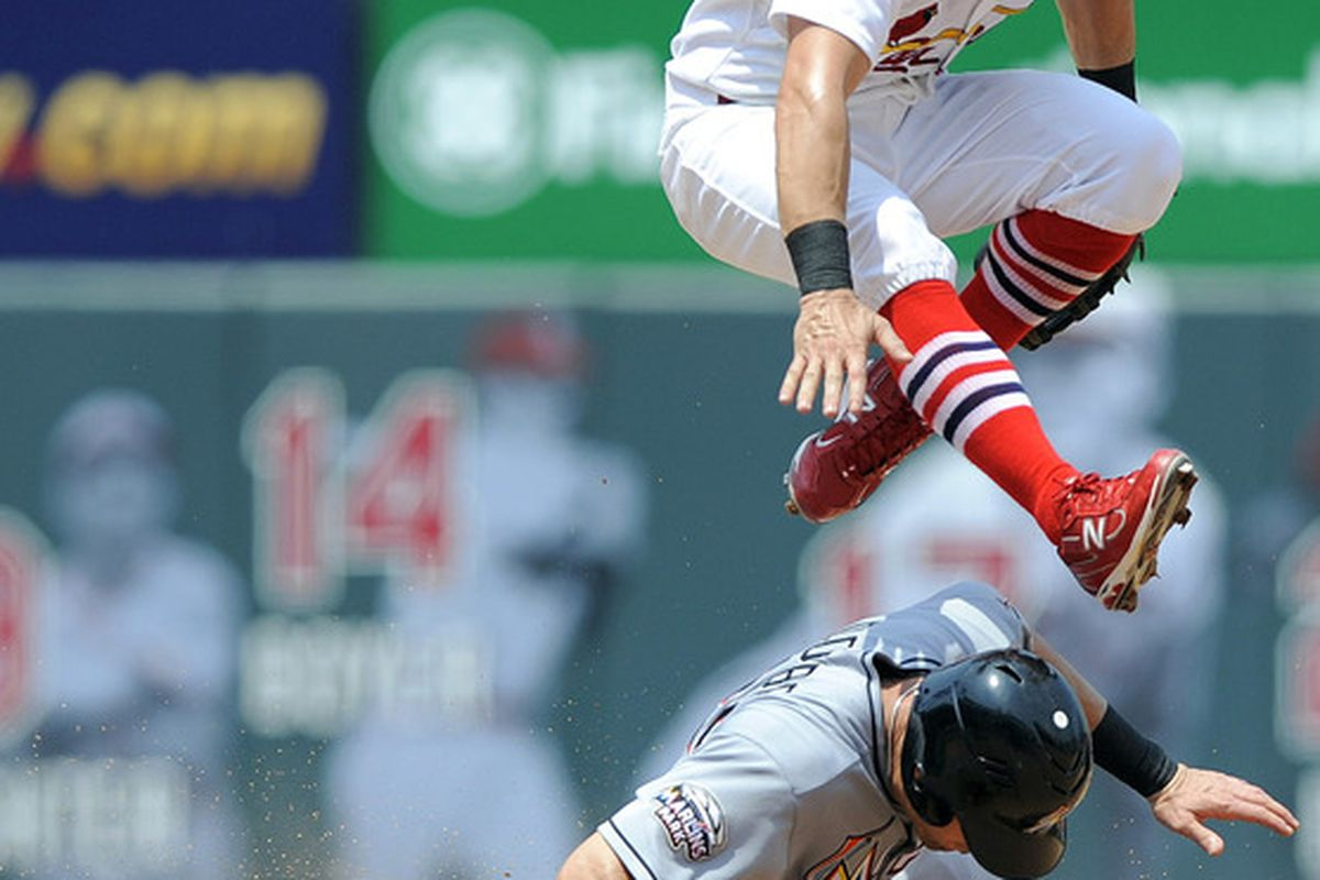 July 8, 2012; St. Louis, MO. USA; St. Louis Cardinals second baseman Skip Schumaker (55) leaps over Miami Marlins right fielder Greg Dobbs (29) in the fourth inning at Busch Stadium. Mandatory Credit: Jeff Curry-US PRESSWIRE