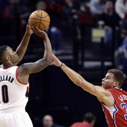 Portland Trail Blazers guard Damian Lillard, left, shoots over Los Angeles Clippers forward Blake Griffin during the first half of an NBA preseason basketball game in Portland, Ore., Monday, Oct. 7, 2013.