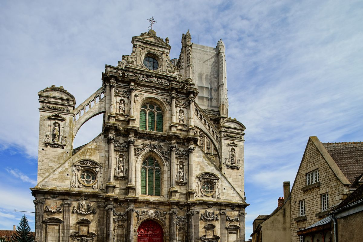 """The exterior of <span data-author=""""843"""">Saint-Pierre church in France.  The facade is concrete and is ornately decorated. </span>"""