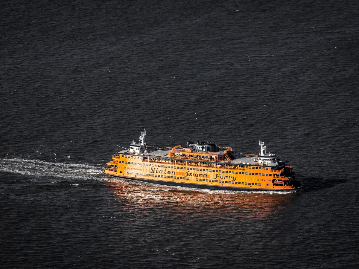 """An orange ferry boat sailing across a body of water. The words """"Staten Island Ferry"""" are painted across the side of the boat."""