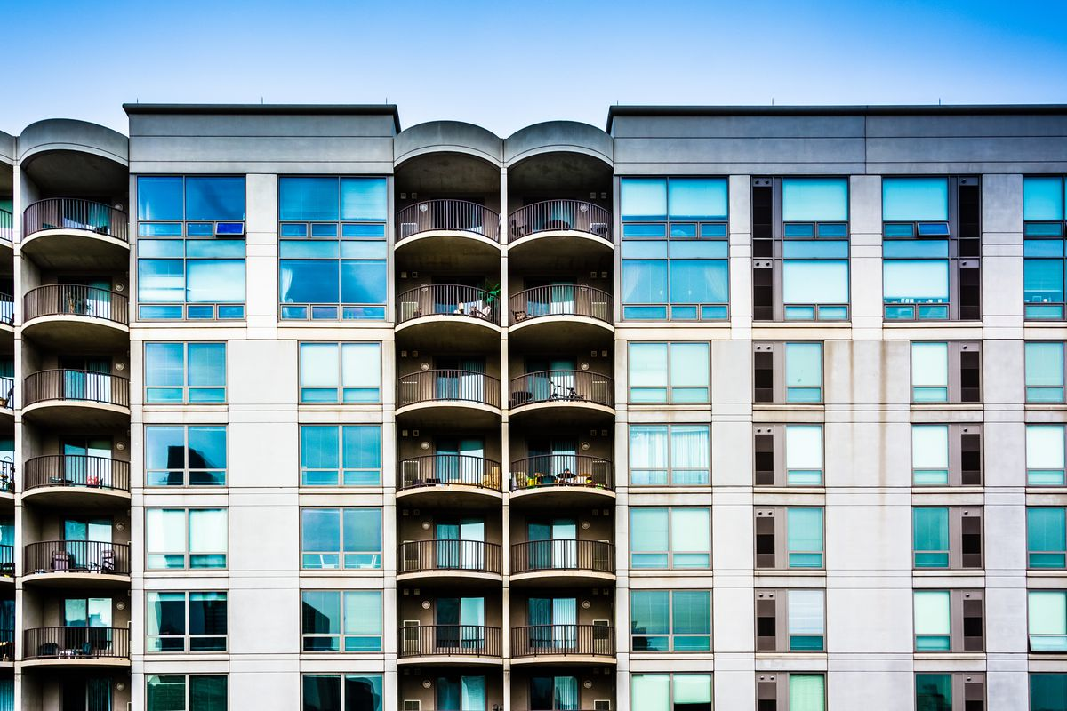 A glassy apartment building with balconies.