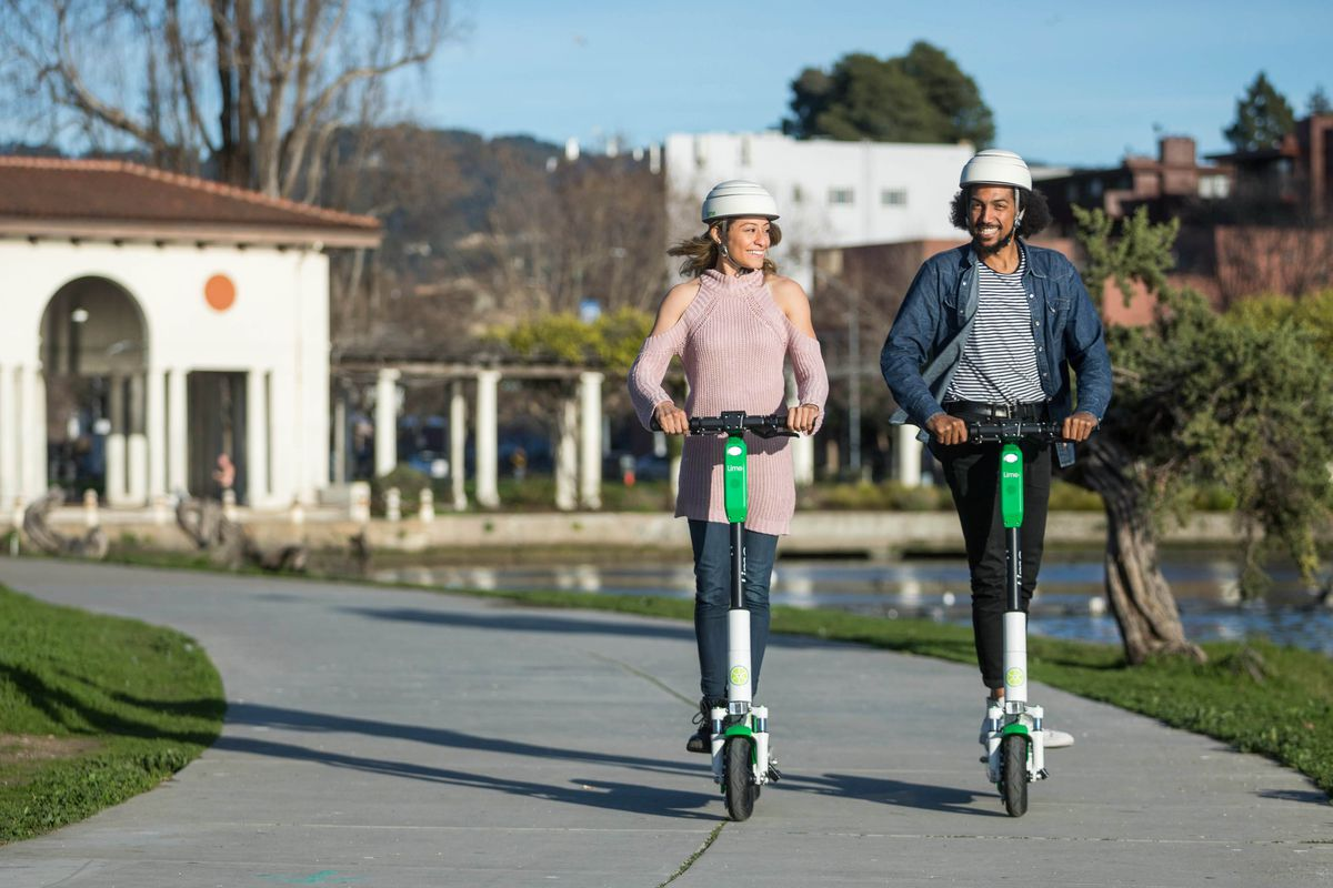A man and woman, both wearing helmets, each riding their own electronic scooter.