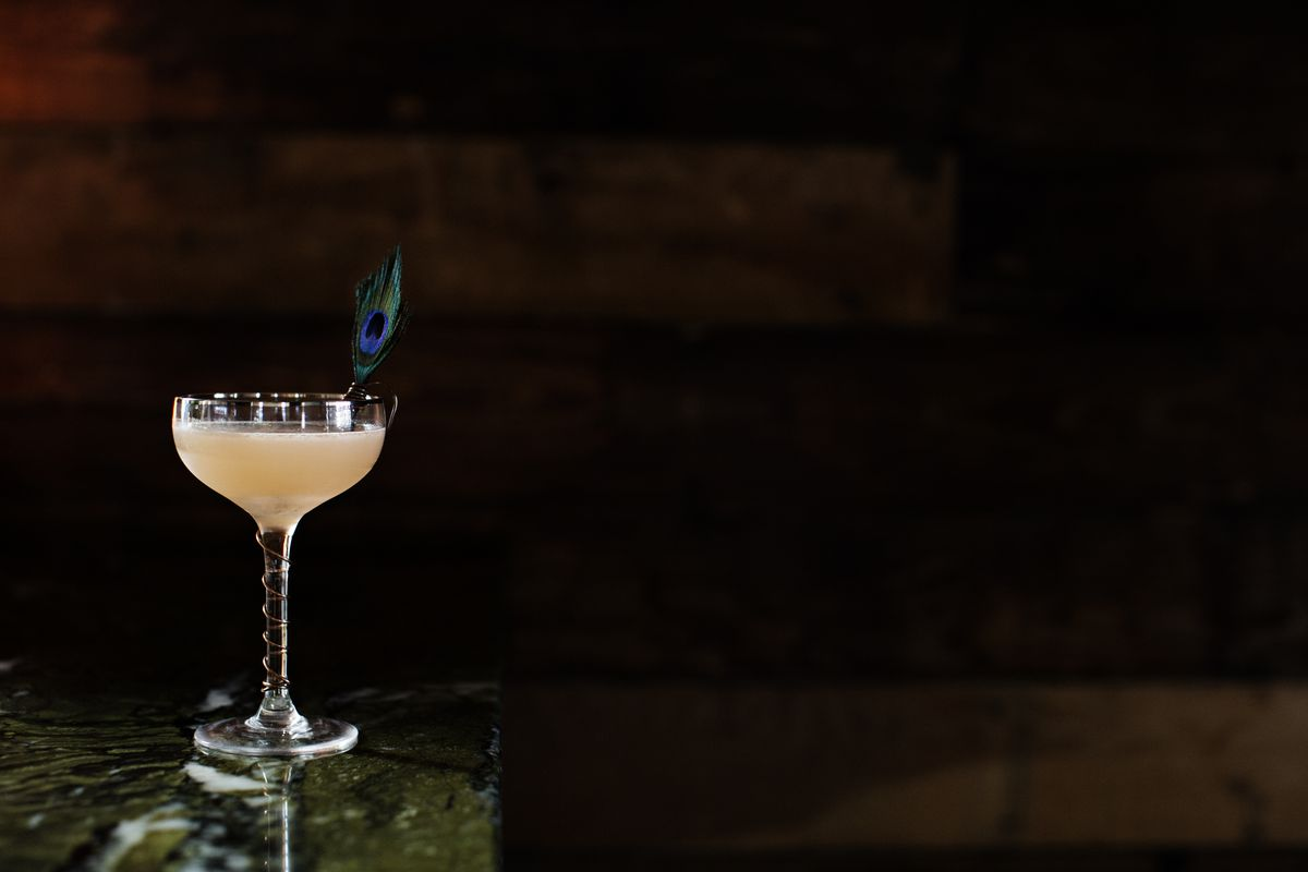 A striking image of the Naked Ballerina cocktail at Martina. A pink beverage in a coup glass is garnished with a peacock feather in front of a darkened wood wall on a green stone bar top