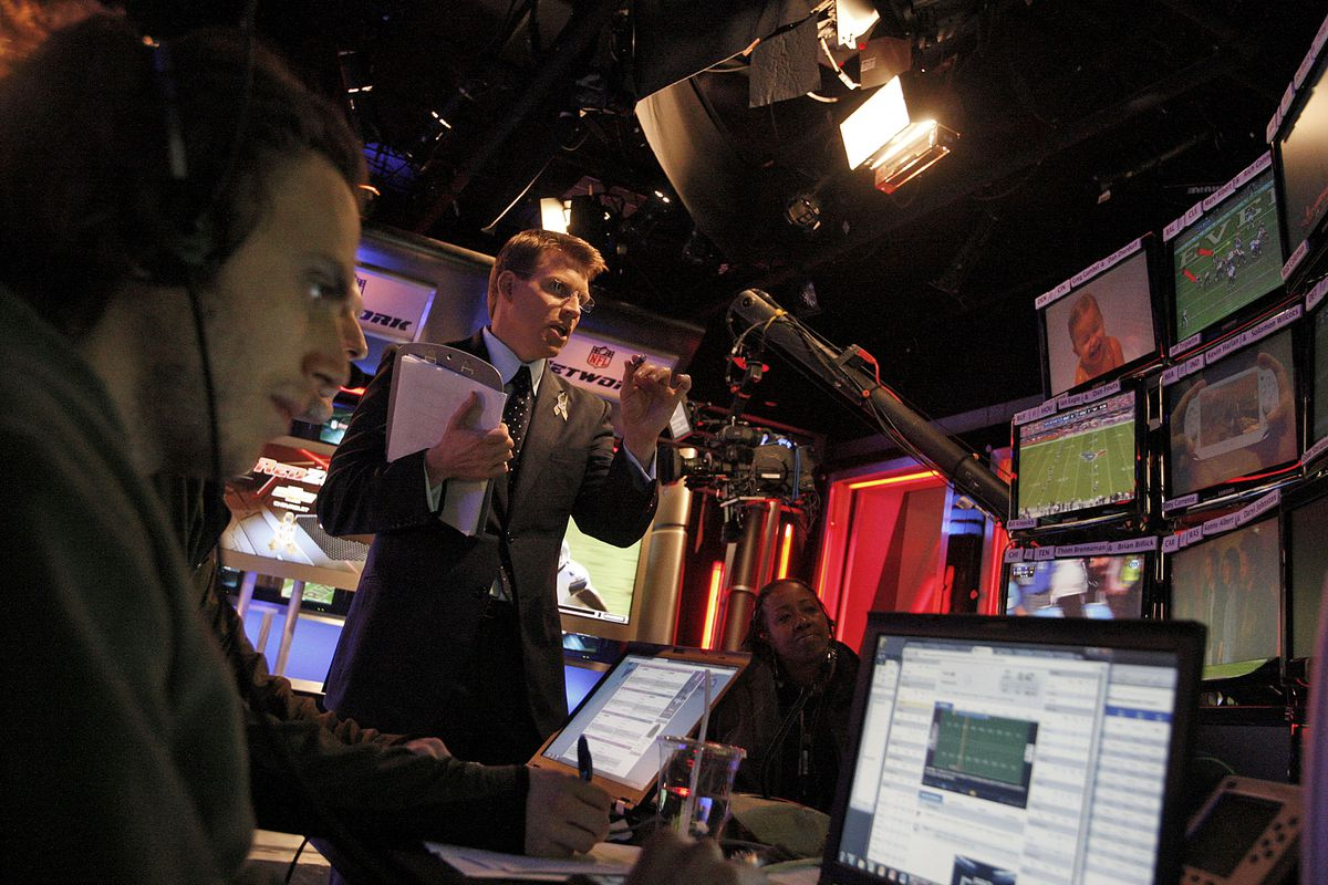 Scott Hanson (middle), lead anchor for the NFL RedZone network, is photographed during the Sunday b