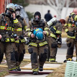 Firefighters clean up after battling a house fire in Taylorsville on Saturday, March 13, 2021. Unified fire officials confirmed one person died in the fire.
