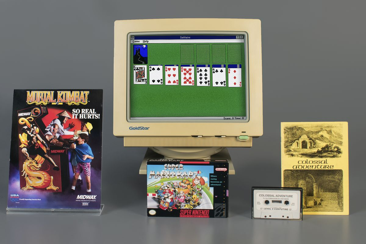 group shot of Mortal Kombat box, Microsoft Solitaire on old CRT monitor, Super Mario Kart original packaging, and Colossal Cave Adventure box and magnetic cassette