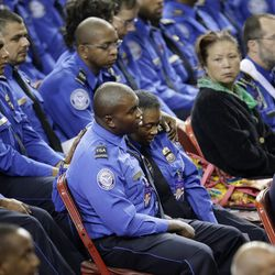 Injured Transportation Security Administration officer Tony Grigsby, center left, is comforted by his mother Faye May who is also a TSA officer during a public memorial service for TSA officer Gerardo Hernandez, who was killed by a rampaging gunman at the Los Angeles International Airport, on Tuesday, Nov. 12, 2013, in Los Angeles. Grigsby was shot twice in the right foot in the recent shooting at the airport.