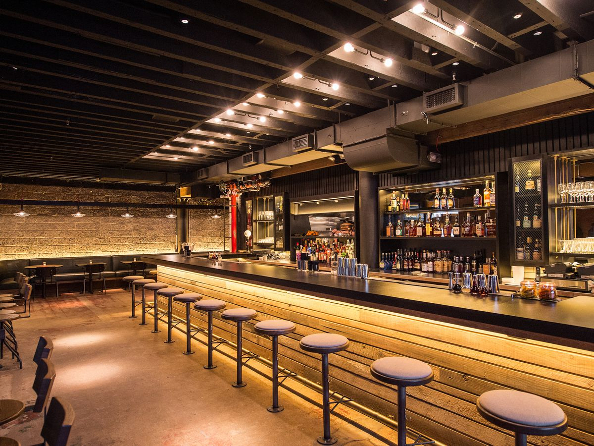 A long bar with lots of golden lighting and stool seating