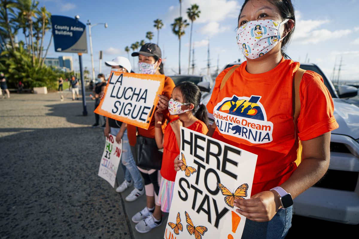 """A line of people stand outdoors in front of parked vehicles, holding signs in English and Spanish. In the front of the line is a young woman and child wearing masks and matching orange shirts, with a sign reading """"Here to Stay""""."""