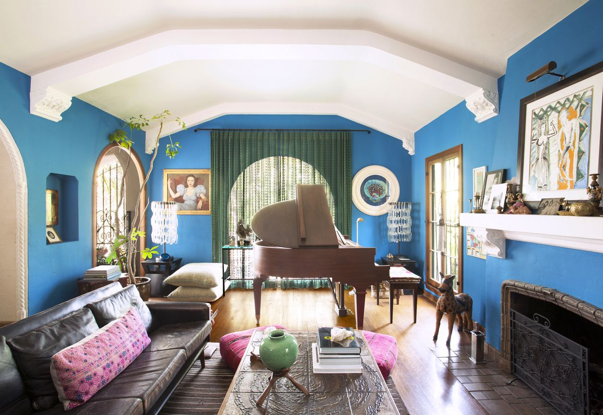 Living room painted bright blue, with white ceilings and beams. a green curtain on the window, piano in the room and brown leather couches with pink pillows.