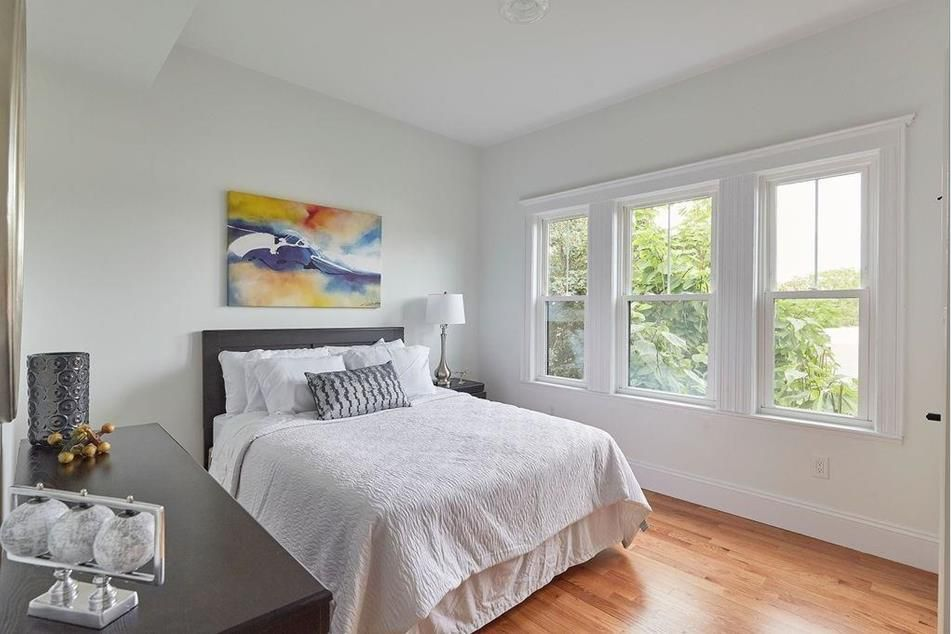 A bedroom with a bed next to three windows.