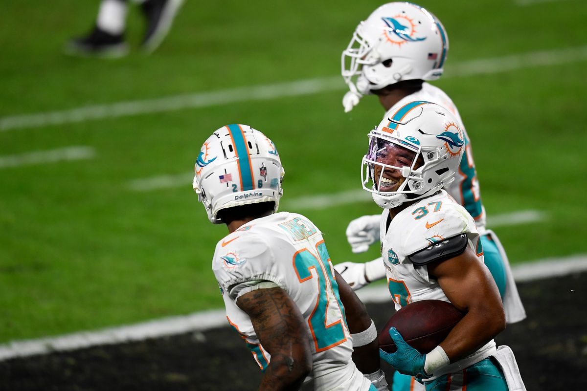 Myles Gaskin #37 of the Miami Dolphins celebrates a touchdown with Salvon Ahmed #26 during the third quarter of a game against the Las Vegas Raiders at Allegiant Stadium on December 26, 2020 in Las Vegas, Nevada.