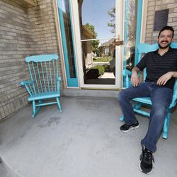 In this Wednesday, June 14, 2017, photograph, Danny Aguilar takes a seat in one of the rocking chair on the front porch of his home in Lakewood, Colo. Aguilar, like nearly half of Americans surveyed in a new poll conducted by The Associated Press-NORC Center Public Affairs Research, said they will not be taking a vacation this summer because they can not afford it or can not get time away from the job.