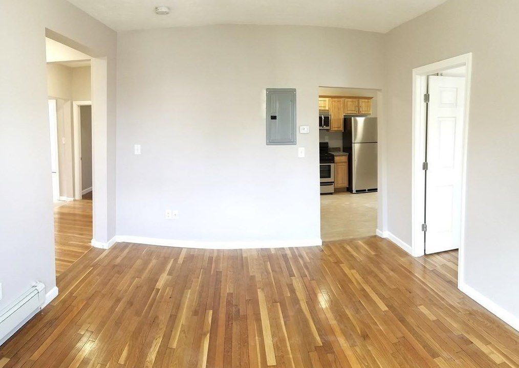 An empty room with three doors leading off it, including into a kitchen.
