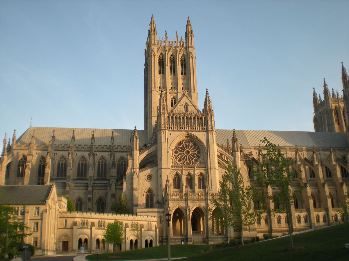 A huge gothic cathedral shown from the side. The sun sets on the cathedral.