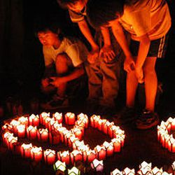 Children look at lit candles placed at a Tokyo park Thursday, marking the second anniversary of the Sept. 11 terror attacks on the United States. Volunteers placed a total of 1,800 candles in the shape of peace signs in remembrance of the victims.