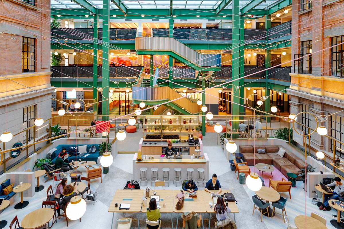 Interior of cavernous industrial space with atrium and exposed steel beams painted green. Two levels of balconies look down on the courtyard that is lit from above from a ceiling of skylights.