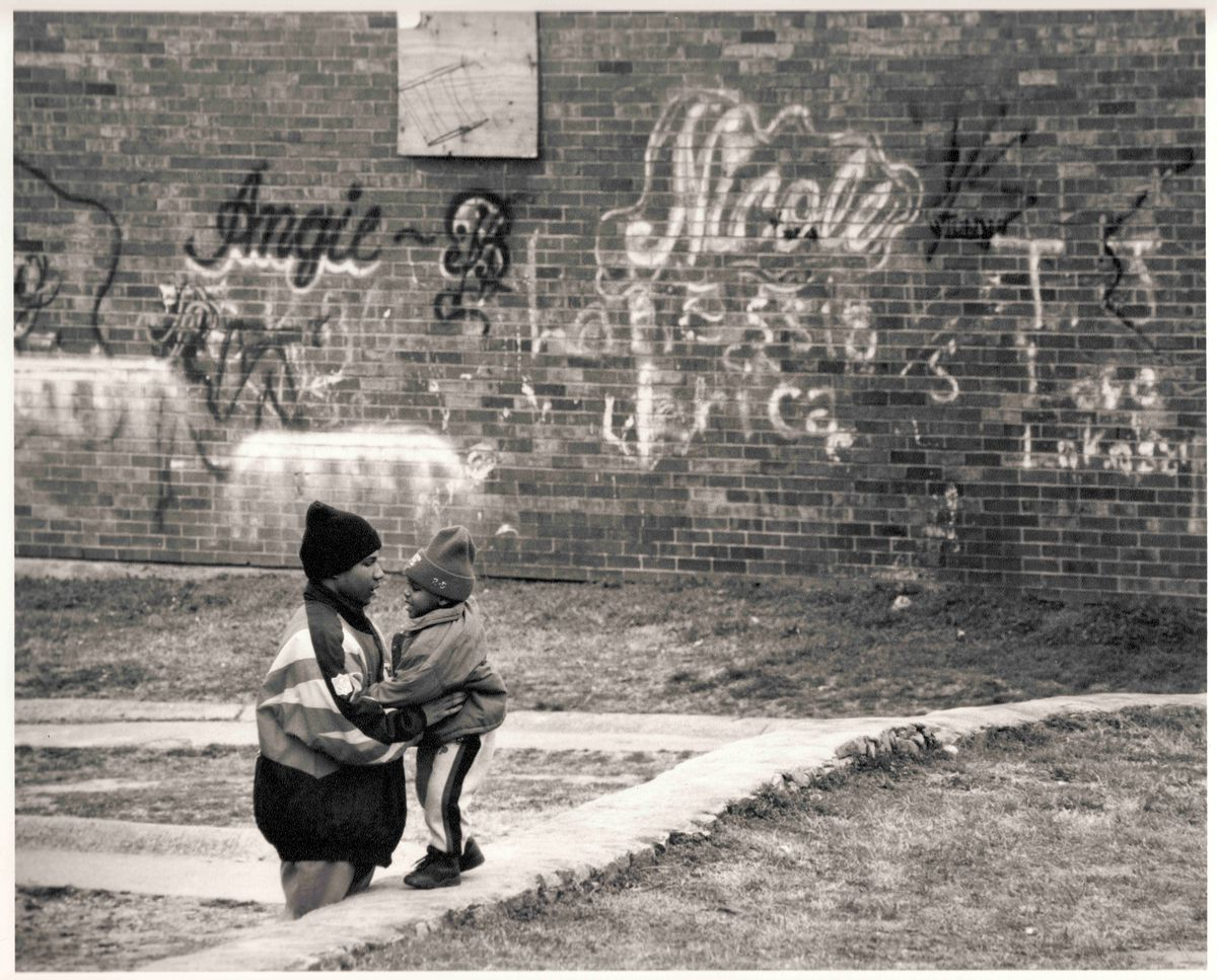 A wall of graffiti and a man and child standing in front of it.