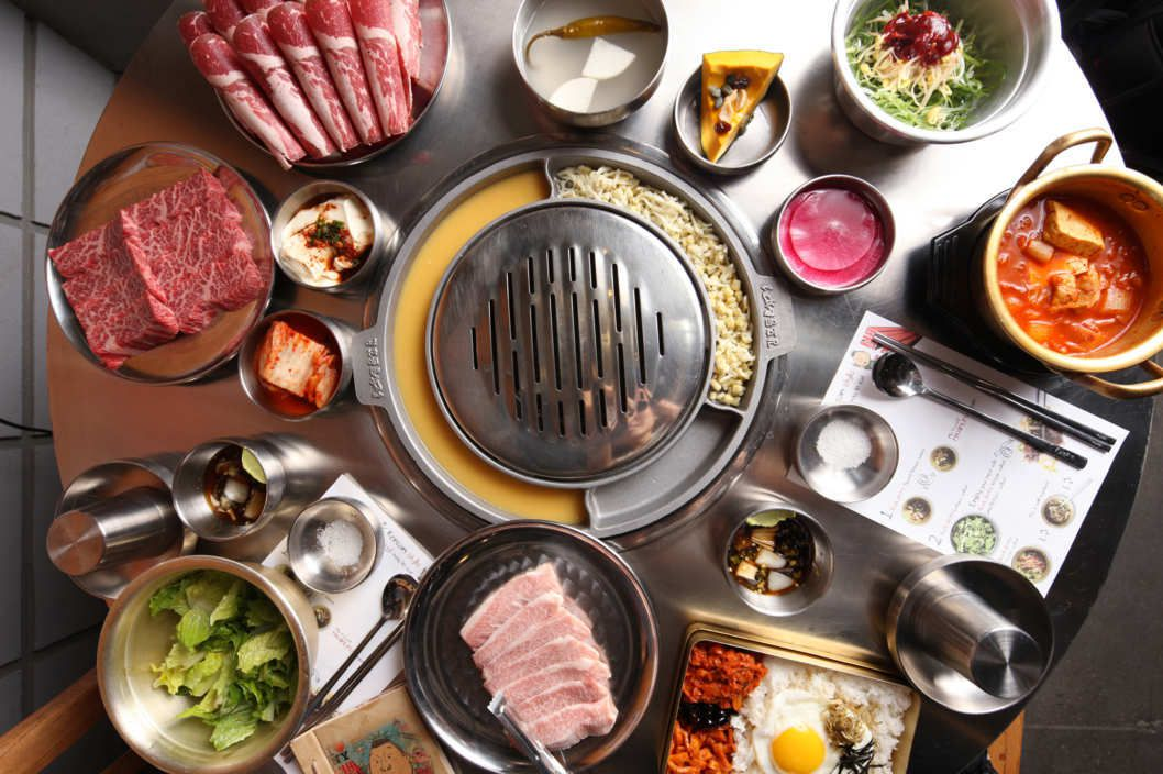 A table with a grill and a spread of banchan and Korean barbecue meats
