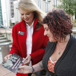 State Senator Jean White, shows photographer Kristina Hill, right, a brochure with an altered  photograph that she took of Tom Privitere and his partner Brian Edwards outside the federal courthouse in Denver on Wednesday, Sept. 26, 2012. Privitere, Edwards and Hill filed a lawsuit in federal court on Wednesday over the fact that the photo was altered and used in a political campaign in Colorado.