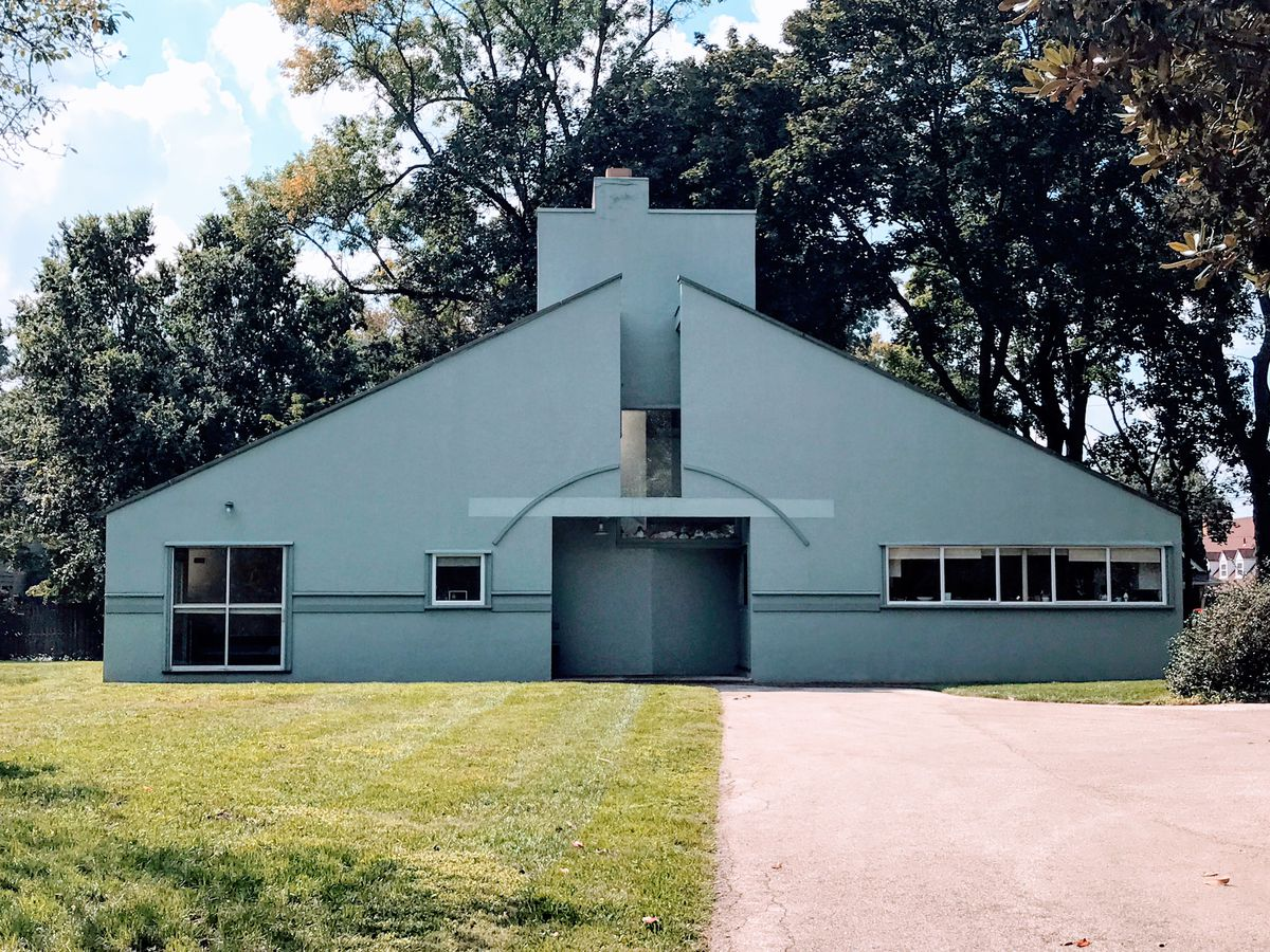 The exterior of the Vanna Venturi house in Philadelphia. The house has a sloped roof and a white facade.