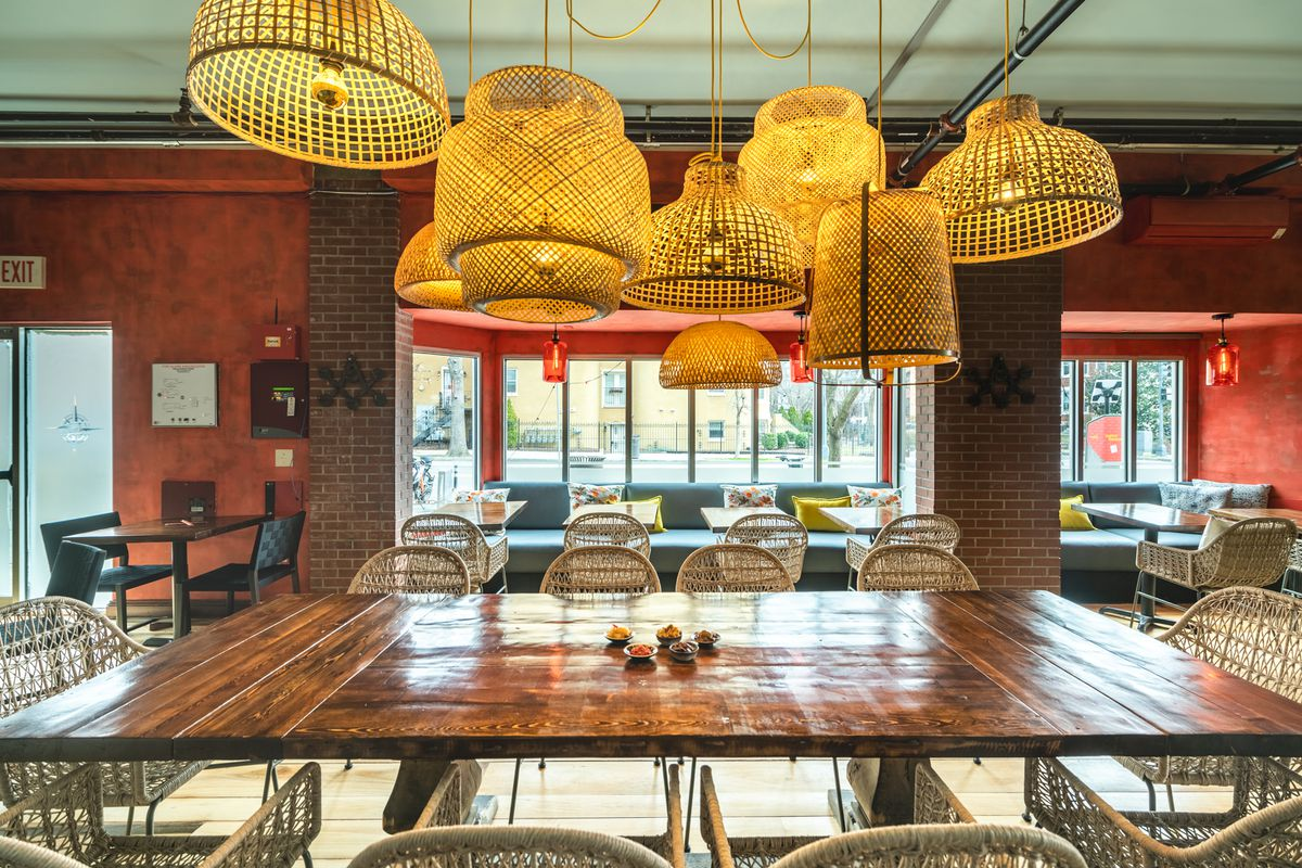 Basket lights hang over a large wooden table at Makan