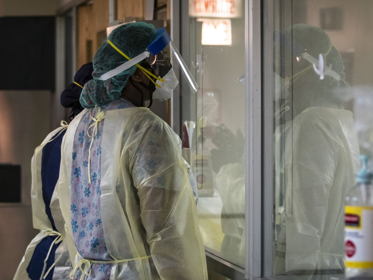 Nurses look through a window as they check on a man with COVID-19 last year in the Intensive Care Unit at Roseland Community Hospital. Illinois recorded its worst one-day coronavirus death toll in nearly six months Wednesday.