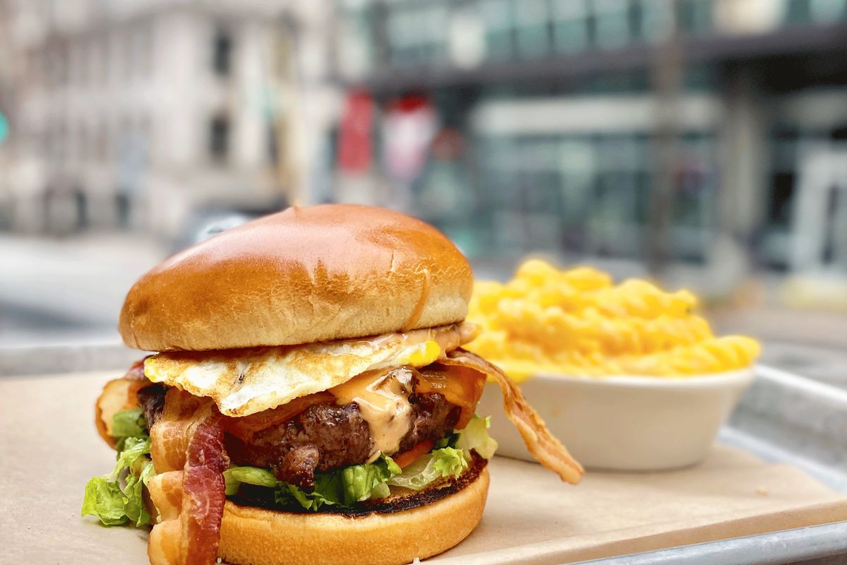 The bacon cheeseburger topped with a fried egg and a side of mac and cheese at Hudson Grille Brookhaven atlanta