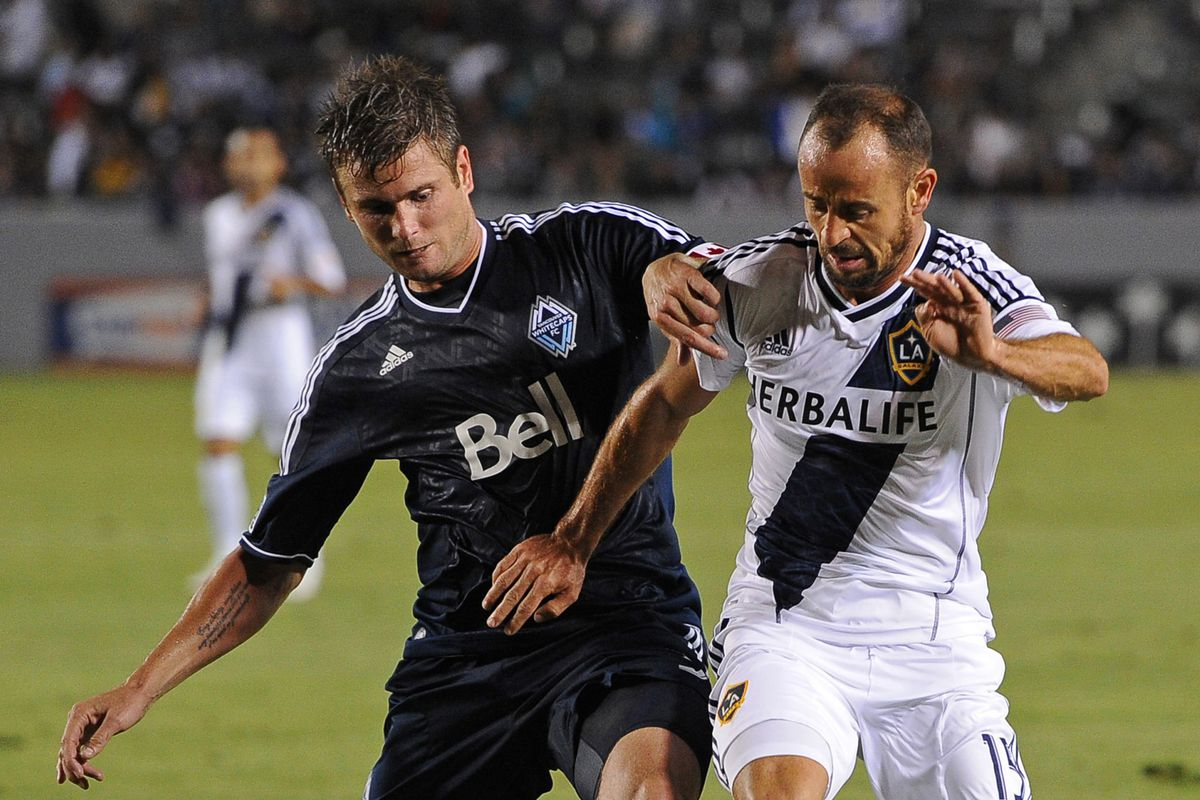 Vancouver's Brad Rusin (L) defends against Los Angeles Galaxy midfielder Laurent Courtois in second half play.