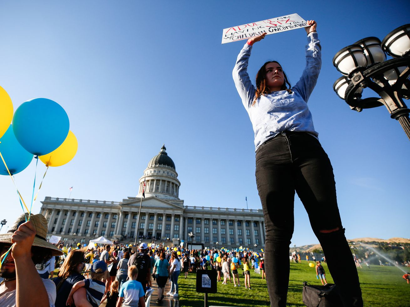 A protester hoists a sign during a protest at the Capitol in Salt Lake City on Thursday, July 30, 2020. The protest was held to commemorate World Human Trafficking Awareness Day and raise awareness about human trafficking.