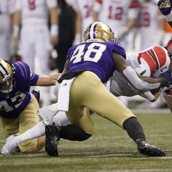 Utah quarterback Jake Bentley, right, dives for extra yardage as he is tackled by Washington linebacker Edefuan Ulofoshio (48) on a keeper play during the first half of an NCAA college football game, Saturday, Nov. 28, 2020, in Seattle.