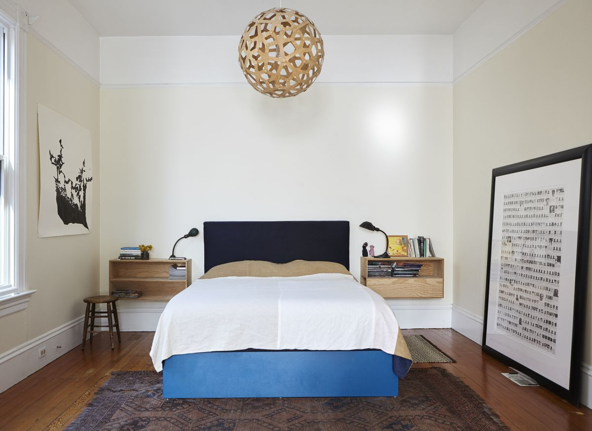 George's bedroom, with a blue bed frame, large wooden light fixture, and black and white art.