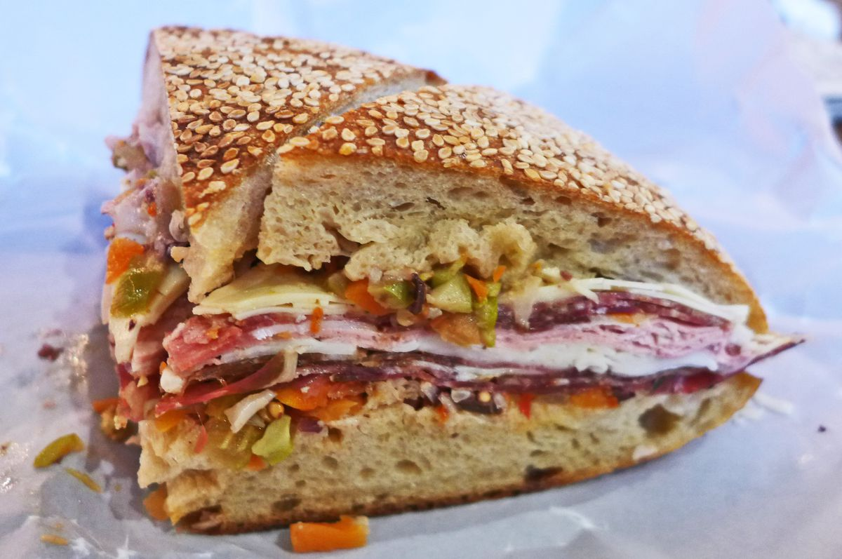 A quarter wedge of round sesame bread piled with cold cuts