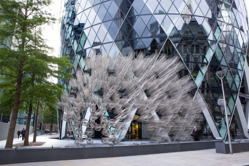 A large, silver-looking abstract sculpture outside a mirrored building