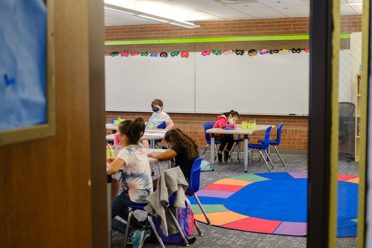 Students sit at tables in a classroom, with a colorful circle-shaped rug dominating the photo.