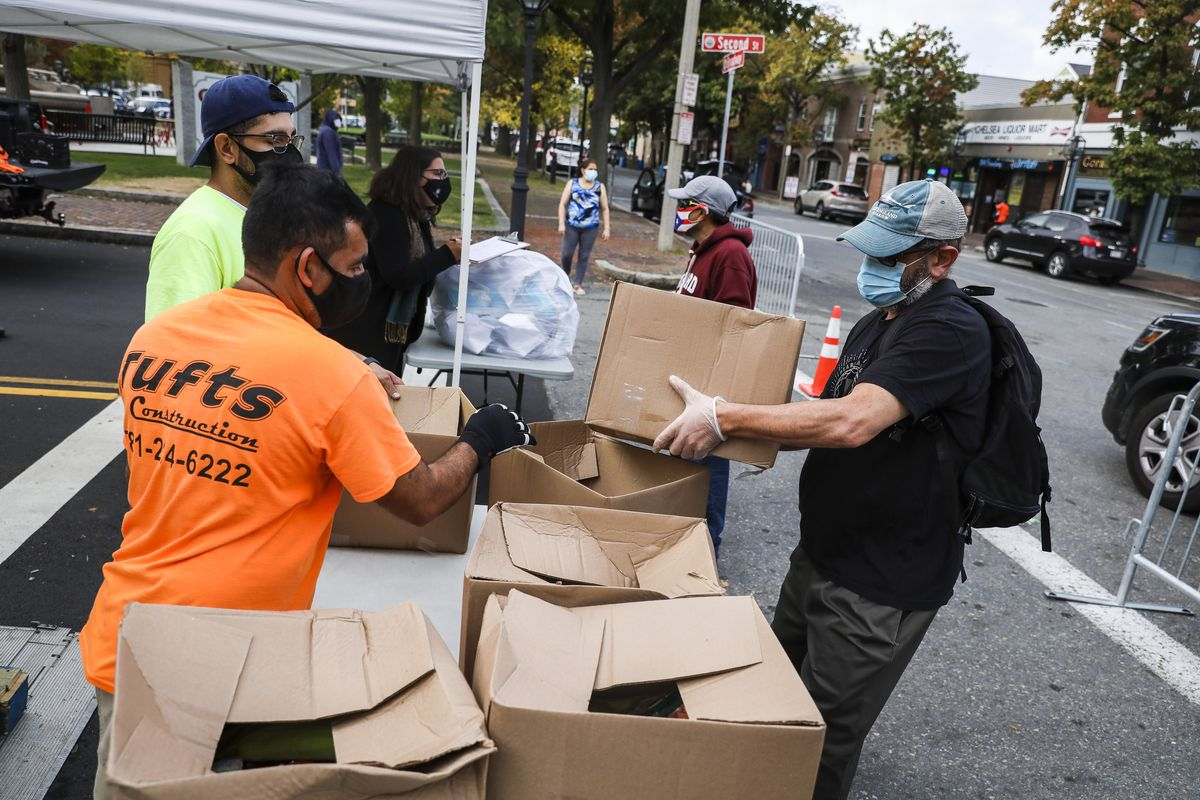 People pick up large cardboard boxes of food at a food bank located on a street.