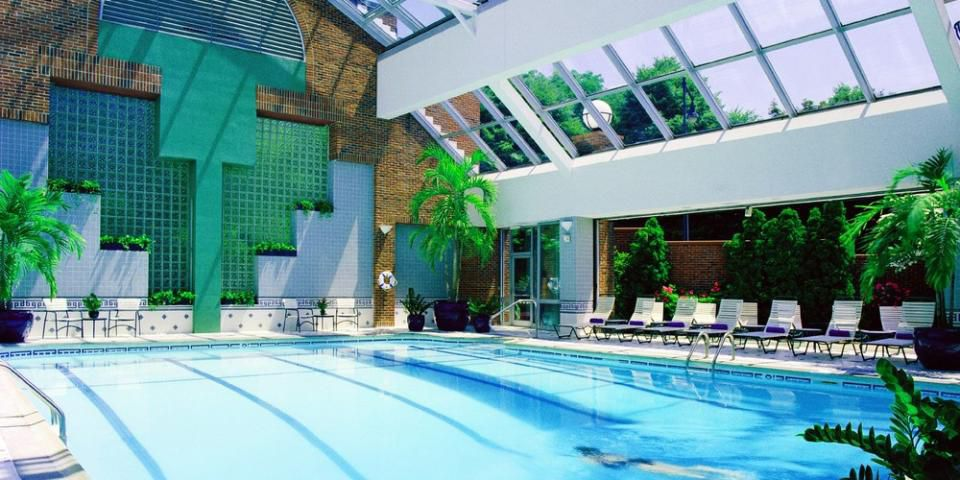 An indoor pool. The walls have multiple windows letting in natural light.