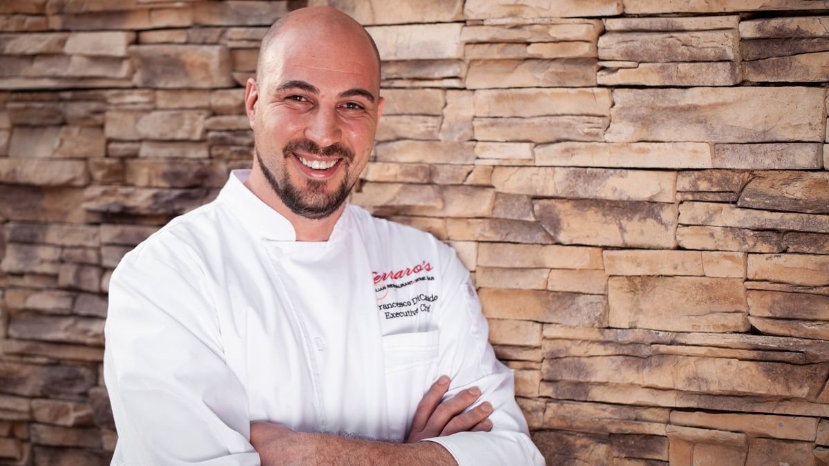 A chef wearing a white coat with his arms crossed