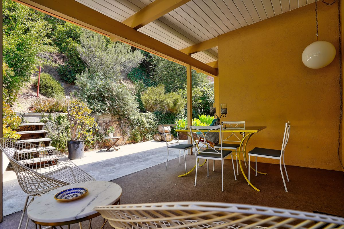 A covered patio with a small dining set, overlooking a tiered garden.
