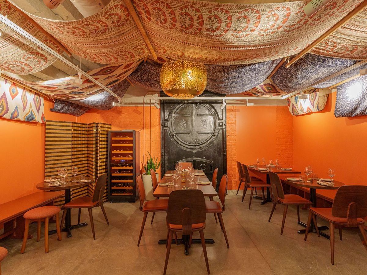 An orange-painted dining room with a draped cloth ceiling.