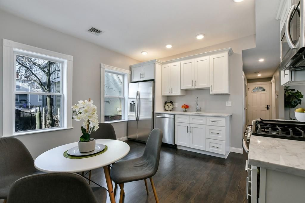 An open kitchen with a table and chairs.