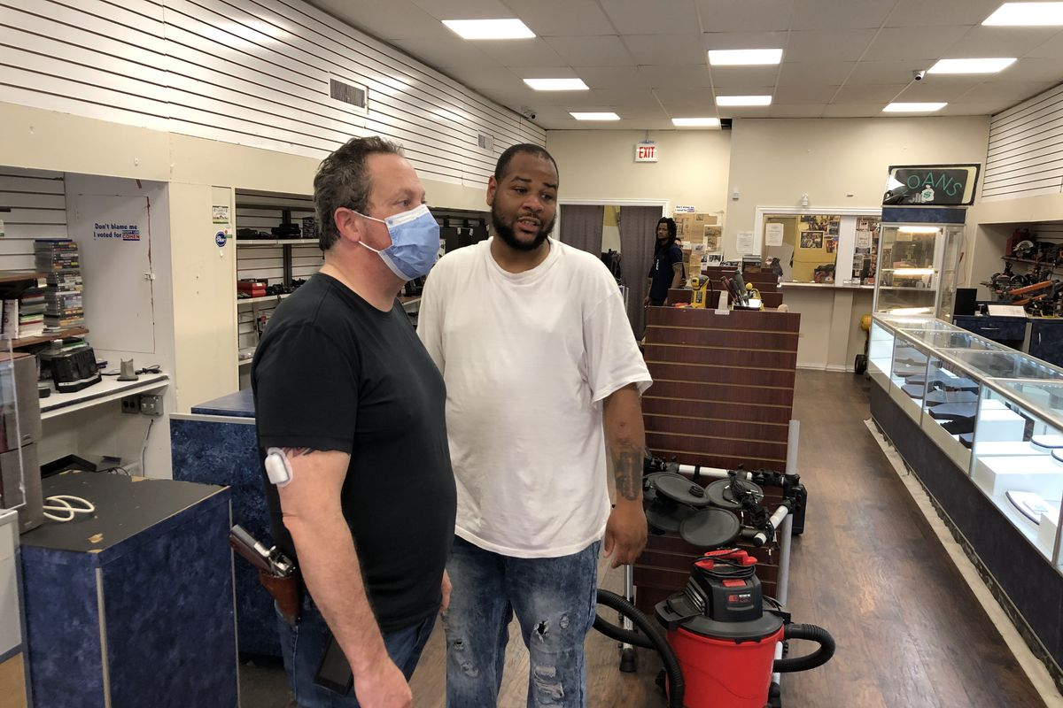 Pawnbroker Scott Lee Cohen, left, and his employee Robert Ross recount the May 31 break-in at his pawn shop at 90th and Commercial in South Chicago.