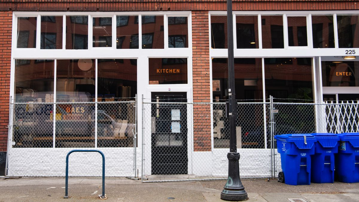 """A building with a chain-link fence with the word """"kitchen"""" on the wall"""